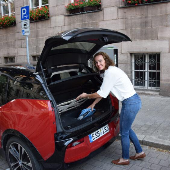 Eine Frau, die ein Ladekabel aus einer Kofferraumverlängerung herausnimmt